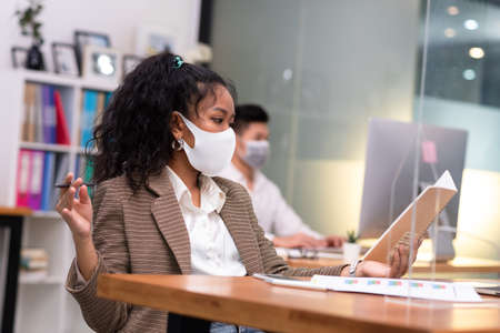 Colored skin woman wearing mask working in iffice taking note