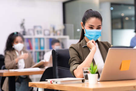 Woman business worker working with laptop wearing flu mask in office show new normal lifestyle