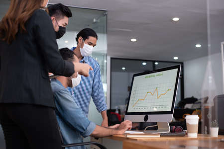 Four asian office worker analysing about kpi social media marketing result while everyone wearing mask as new normal lifestyle Banco de Imagens