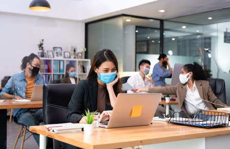 Woman business worker sending document to co-worker wearing flu mask in office show new normal lifestyle