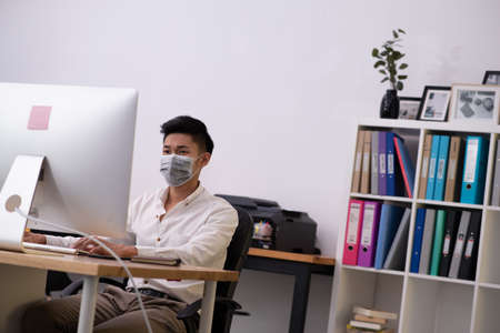 Asian businessman working in office wearing mask with stress emotion