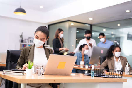Five office worker have a small meeting brainstorm together with everyone wear mask as new normal lifestyle