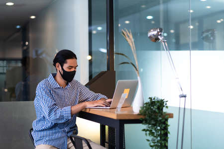 Asian man working with laptop wearing mask in office