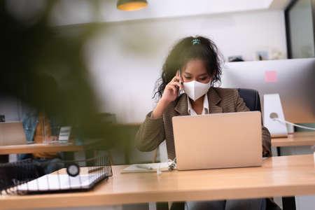 Colored skin woman wearing mask working in iffice calling customer via smartphone
