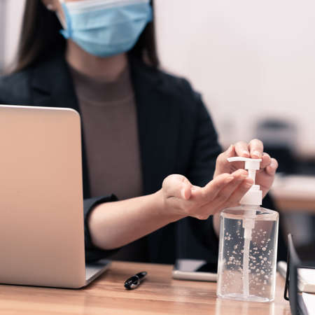 Asian woman office worker use alcohol gel to clean her hands
