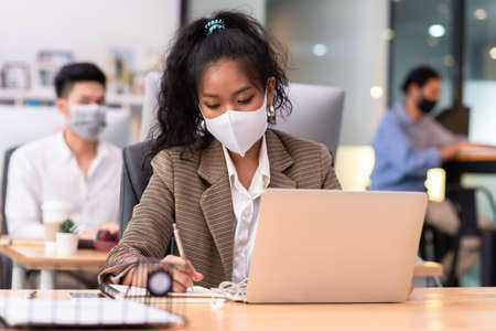 Colored skin woman wearing mask working in iffice taking note and use laptop