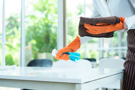 Woman restaurant staff cleaning table with alcohol spray wearing glove, face shield and mask before open the restaurant Stock fotó