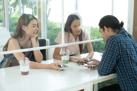 Group of three people see each other in cafe with plastic partition for social distanccing Banco de Imagens
