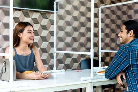Couple in restaurant with plastic partition seperate for social distancing in new normal life style
