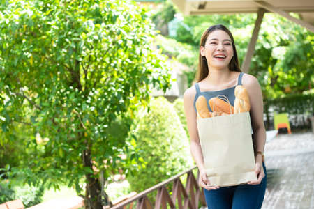 Asian woman hold paper bag of bread