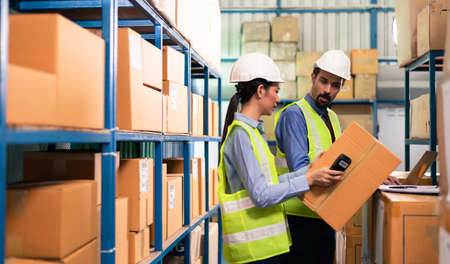 Warehouse woman staff use bar code scanner checking stock and supply on site