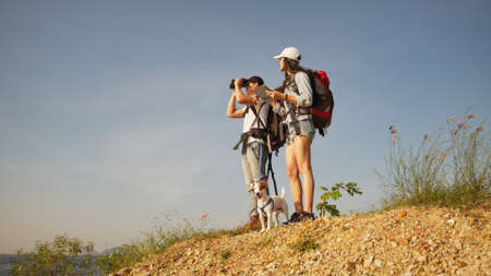 Couple backpacker and their dog on backpacking trip reach destination use binocular and tablet to navigate the way 版權商用圖片