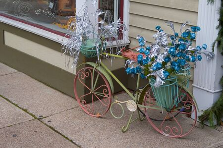 Floral decorated Victorian style bicycle outside shop.