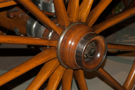 spoked: Detail of the wood spoked wheel on a wagon.