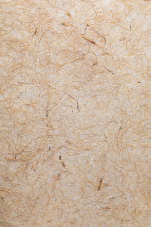 Handmade paper texture with vegetable fibers like straw. In delicate tones, yellows, oranges, browns and vanilla. Stock Photo