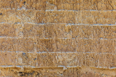 Wall of adobe, earth, mud, straw, pressed. Old, traditional and sustainable construction. Eroded by the passage of time and weather. Stock Photo