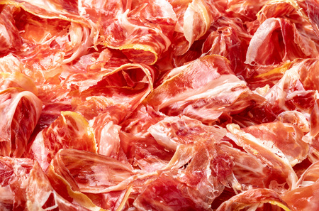 Appetizing slices Iberian ham in the foreground as a texture. Raw meat that becomes an article of haute cuisine and gastronomic luxury, through a process of raw salting and natural curing. Banque d'images