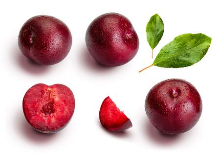 Prunes sous différents angles et feuilles isolées sur fond blanc. Prunes rouges appétissantes et saines, entières et coupées en segments avec un aspect d'illustration.