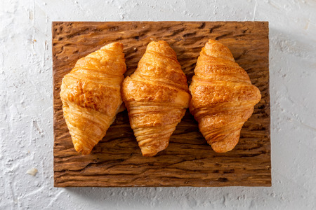 Butter croissants on a rustic wooden board. Aerial view on light background.