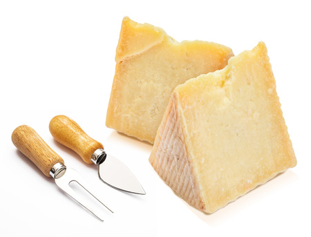 Cured sheep cheese (Manchego type) in wedge and cutlery. Isolated on white background.