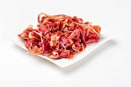 Appetizing slices Iberian ham on a plate. Isolated on white background. Raw meat that becomes an article of haute cuisine and gastronomic luxury, through a process of raw salting and natural curing. Stock fotó