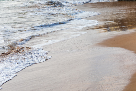 Waves on the beach on a sunny day and calm sea. Beautiful ocher, brown, blue and white tones.