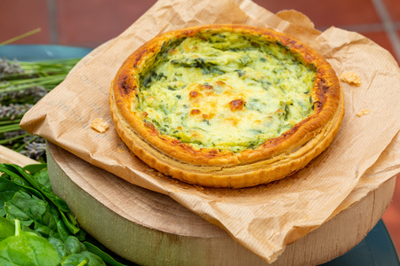 Close-up of quiche with fresh vegetables. Background in green tones. Rustic and country aspect.