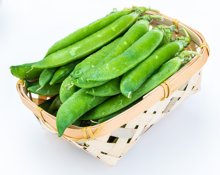 Green, tender, fresh and raw peas. In wicker basket. Isolated on white background.