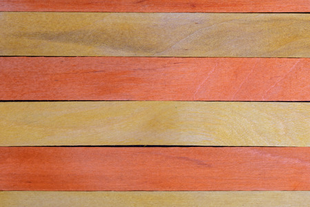 Beautiful texture of natural wood slats of orange and yellow colors. Natural and aged appearance.