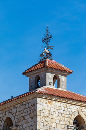 Couple of storks making a nest on the steeple of a church. Sunny day and blue sky.