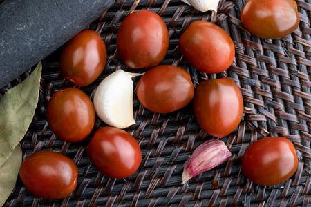 Cherry tomatoes mini Kumato, garlic and laurel. Rustic appearance. Banco de Imagens