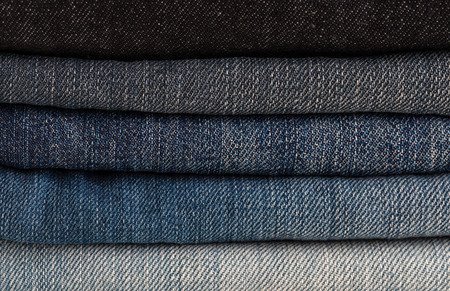 Heap of jeans of various shades. Close-up. Banco de Imagens