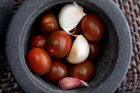 Cherry tomatoes mini Kumato, garlic and laurel. In stone mortar. Rustic appearance. Banco de Imagens