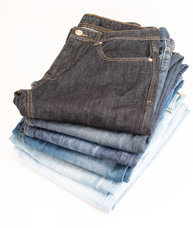 Heap of jeans of various shades. Isolated on white background. Banco de Imagens