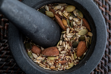 Close-up with mix of seeds and nuts. In stone mortar. Rustic appearance.