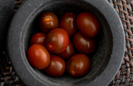 Cherry tomatoes mini Kumato. In stone mortar. Rustic appearance. Banco de Imagens