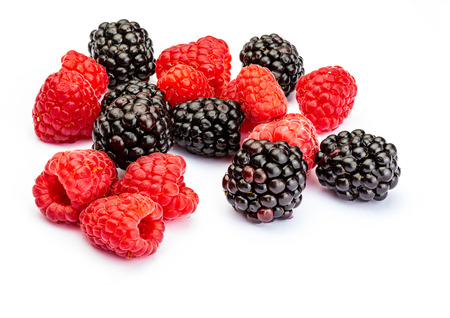 They look like artificial treats! But they are delicious and beautiful blackberries and fresh raspberries. Isolated on white background. Foto de archivo