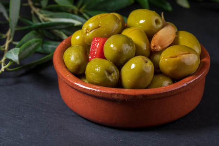 Clay pot with artisan olives (preserved in extra virgin olive oil, vinegar, spices) with red peppers and garlic. Includes leaves of the olive tree. Appetizer concept. On black chalkboard background. Фото со стока
