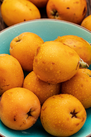 Fresh loquats (medlars) in blue turquoise bowl. Rustic and healthy appearance. Close-up.Top view. Banco de Imagens