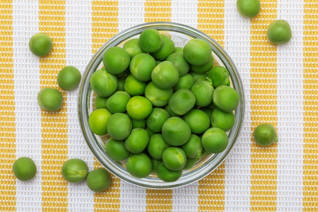 Green, tender, fresh and raw peas. Close-up and top view.
