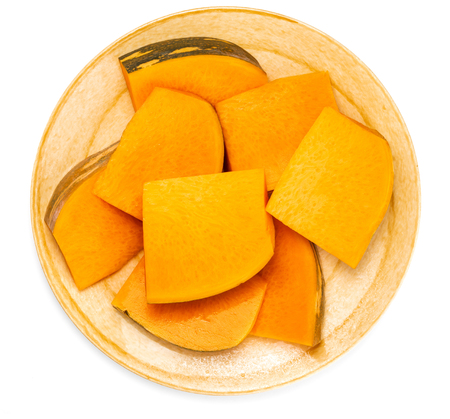 Plate with pieces of fresh pumpkin isolated on white background. Top view.