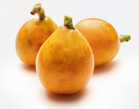 Three fresh loquats (medlars). Isolated on white background. Close-up.