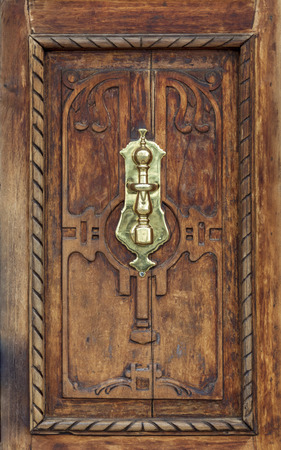 Precious wooden door aged by time. Bronze caller (gold). Banco de Imagens