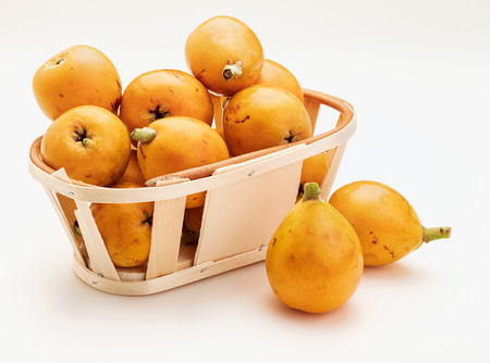 Fresh loquats (medlars) in wicker basket. Isolated on white background. Close-up. Banco de Imagens