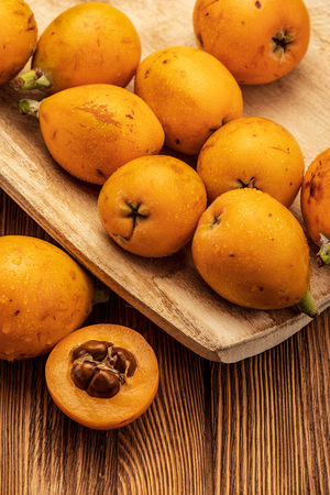 Fresh loquats (medlars) on wooden background. Rustic and healthy appearance. Close-up.Top view.
