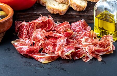 Appetizing slices Iberian ham in the foreground. Olive oil, bread, fresh tomato, olives. Black background. Rustic and homemade appearance.
