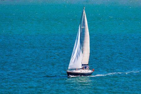 Veliero sportivo che naviga attraverso la baia con mare calmo e cielo blu. Spazio per inserire il testo. Santander (Spagna)