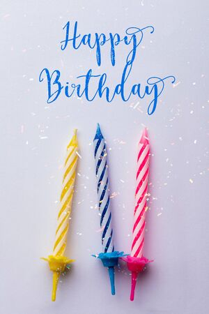 Birthday greeting card. With very colorful candles (red, yellow, white and blue) on a white background. With text Happy Birthday