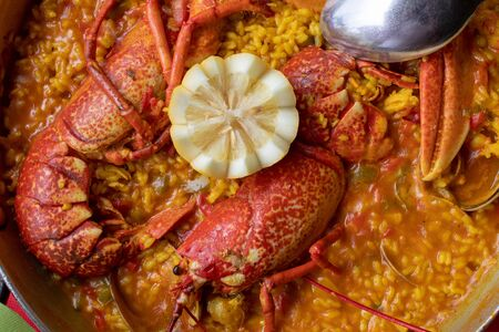 Close-up of creamy rice with lobster, clams and other seafood. Presented in paellera.