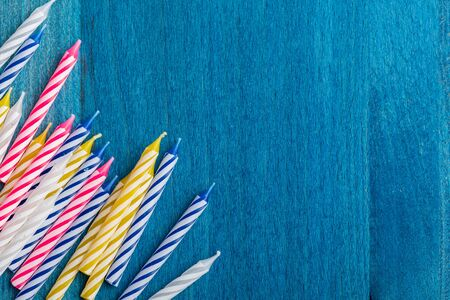 Group of birthday candles on blue wooden background. For birthday greeting card. Space to insert text. Very colorful, with blue, red, yellow and white.